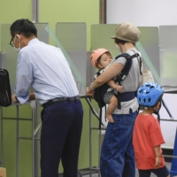 Voters at a polling station for the Yokohama mayoral election on Sunday | KYODO