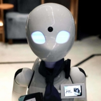 A humanoid robot delivers drinks to customers at the Dawn Cafe in Tokyo on Aug. 17. | AFP-JIJI