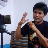Siswanto records a video at his home in a farming community in Banyuwangi, Indonesia.   AFP-JIJI