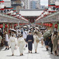 People walk through the Nakamise alley in Tokyo's Asakusa district on Saturday. | KYODO