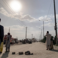 People gather near the airport in Kabul on Saturday.    JIM HUYLEBROEK / THE NEW YORK TIMES