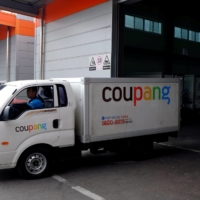 Delivery trucks for e-commerce retailer Coupang leave a distribution center in Seoul, South Korea, in June 2018.   REUTERS