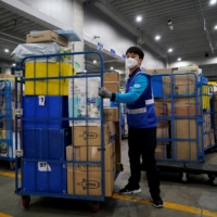 Jung Im-hong, a delivery worker for Coupang, wears a mask as he loads packages before leaving to deliver them in Incheon, South Korea, in March 2020.   REUTERS