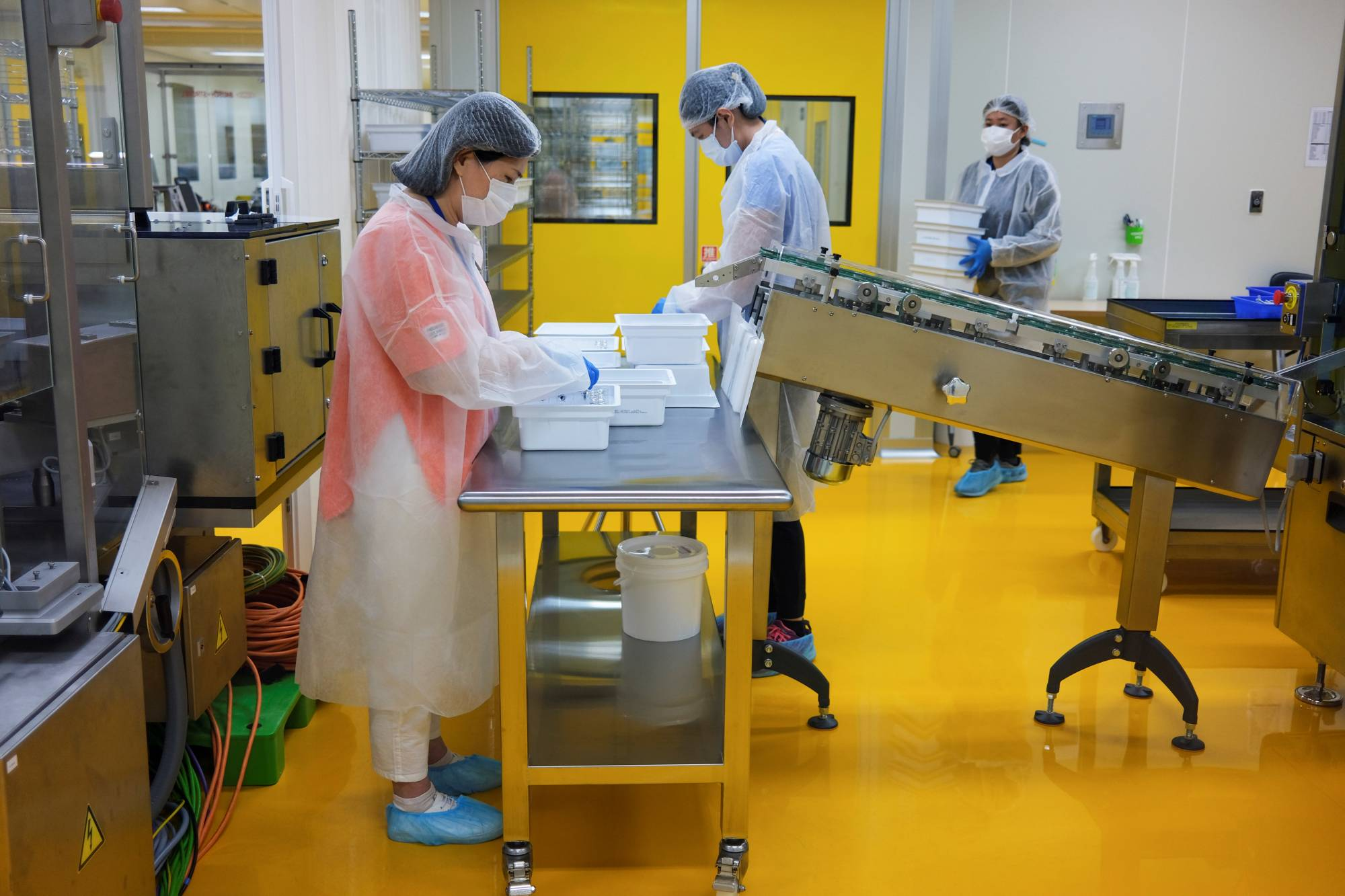 Staff members work on the production line of Medigen's vaccine in Hsinchu, Taiwan, on Aug. 10. | REUTERS