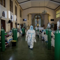 A health worker checks on coronavirus patients inside the chapel of Quezon City General Hospital, which was turned into a COVID-19 ward amid rising infections, in Quezon City, Metro Manila, on Friday. | REUTERS
