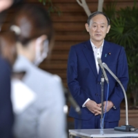 Prime Minister Yoshihide Suga speaks to reporters in Tokyo on Monday. | KYODO