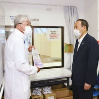 Prime Minister Yoshihide Suga and Tokyo Gov. Yuriko Koike visit a facility in Shinagawa Prince Hotel East Tower on Aug. 16 to get a first-hand look at an 'antibody cocktail' treatment for COVID-19 patients.   KYODO
