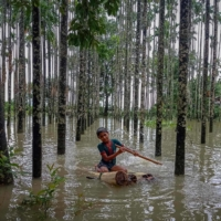 A child wades through a flooded area using a makeshift raft at Maulovir Para, Cox's Bazar, on July 30, after monsoon floods and landslides cut off more than 300,000 people in villages across southeast Bangladesh. | AFP-JIJI