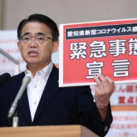 Aichi Gov. Hideaki Omura holds a sign that refers to the COVID-19 state of emergency on Friday as the prefecture called on the central government to place it under the emergency measure.   KYODO