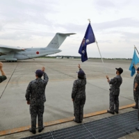 Members of Self-Defense Forces see off a C-2 transport plane bound for Afghanistan from ASDF Iruma Air Base in the city of Sayama, Saitama Prefecture, on Monday.   KYODO
