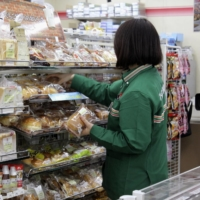 A clerk stocks the shelves at a 7-Eleven store in Tokyo. The chain announced this week its intention to begin experimenting with home delivery of food items and sundries. | KYODO