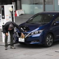 A man cleans an electric vehicle while it is plugged into a charging station in front of the Nissan Motor Co. headquarters in Yokohama. | BLOOMBERG