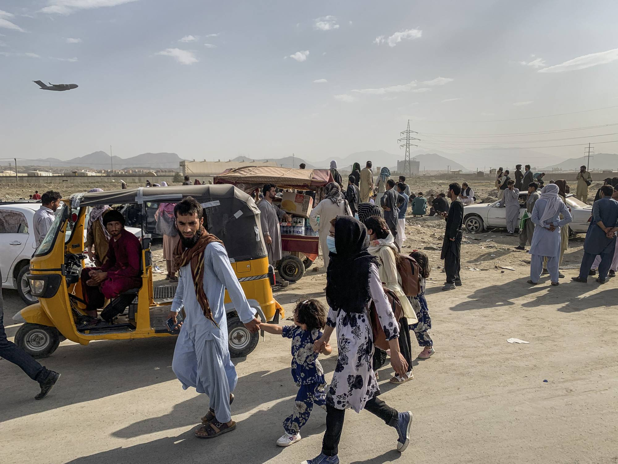 People wait outside Hamid Karzai International Airport in Kabul as a military transport plane takes off behind them on Saturday.  | JIM HUYLEBROEK / THE NEW YORK TIMES