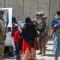 U.S. soldiers assist Afghan civilians during the evacuation effort at the international airport in Kabul on Aug. 20.   U.S. MARINE CORPS / VIA REUTERS