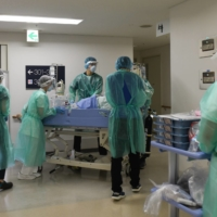 Health care workers transfer a COVID-19 patient to the intensive care unit at Chiba University Hospital in Chiba Prefecture on Wednesday.   BLOOMBERG