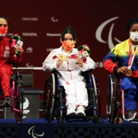 Gold medalist Lingling Guo of China, silver medalist Ni Nengah Widiasih of Indonesia and bronze medalist Clara Sarahy Fuentes Monasterio of Venezuela celebrate after the women's under-41 kg final at Tokyo International Forum.  | REUTERS