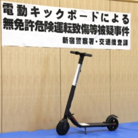 Tokyo police displays a model of the same type of the electric kick scooter as was used by a woman referred to prosecutors Thursday for unlicensed dangerous driving causing injury.