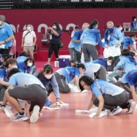 The dirty work: Volunteers clean the floor of the Ariake Arena in Tokyo after a men's volleyball match. | KYODO