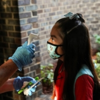 A student has her temperature checked at an elementary school in Houston on Monday.  | REUTERS