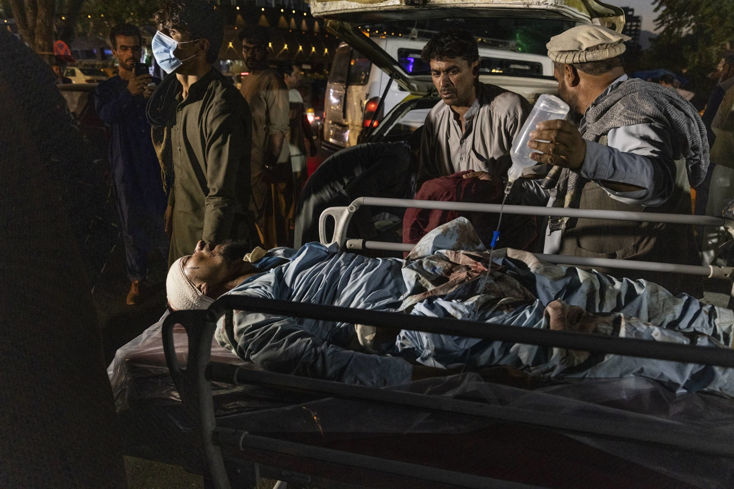 A person wounded in a bomb blast outside the international airport in Kabul arrives at a hospital on Thursday.  | VICTOR J. BLUE / THE NEW YORK TIMES