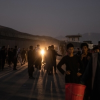 People are sent away from the scene of a bomb blast outside the international airport in Kabul on Thursday.  | JIM HUYLEBROEK / THE NEW YORK TIMES