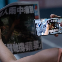 A woman takes a photo of the Apple Daily newspaper's final edition in Hong Kong on June 24.    AFP-JIJI