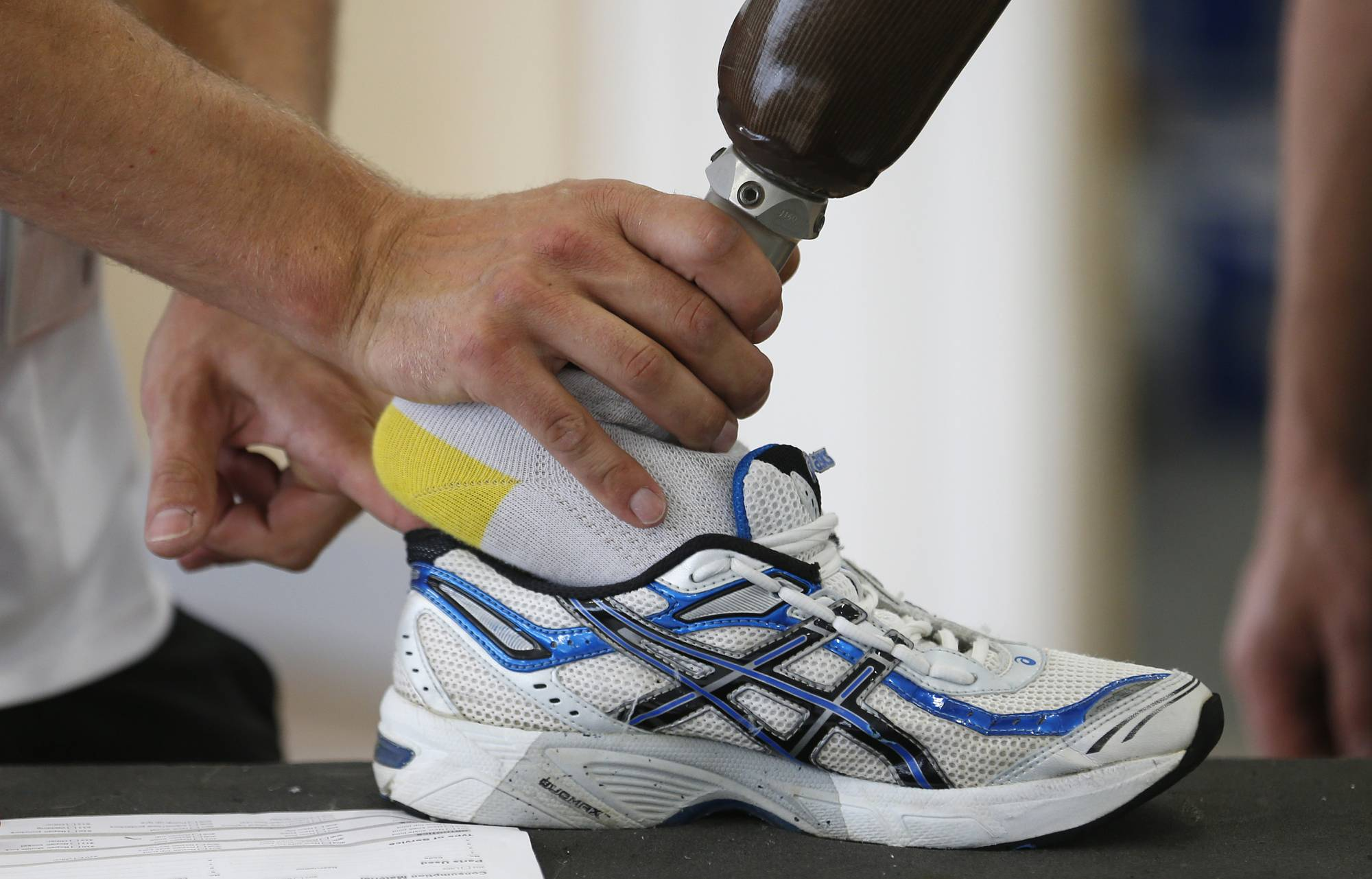 A technician fits a prosthetic foot into a trainer in an Ottobock workshop at the London athletes' village in 2012. | REUTERS