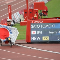 Tomoki Sato poses next to a monitor Friday showing his Paralympic record time of 55.39 seconds in the men's T52 400 meters  | DAN ORLOWITZ
