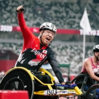 Tomoki Sato reacts after winning the men's T52 400-meter final during he Tokyo Paralympics at the National Stadium on Friday. | KYODO