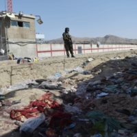 A Taliban fighter on Friday stands guard at the site of the Thursday twin suicide bombs at Kabul airport.   AFP-JIJI