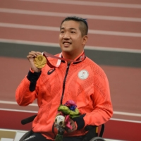 Tomoki Sato celebrates with his gold medal after the men's T52 400-meter final on Friday.  | DAN ORLOWITZ