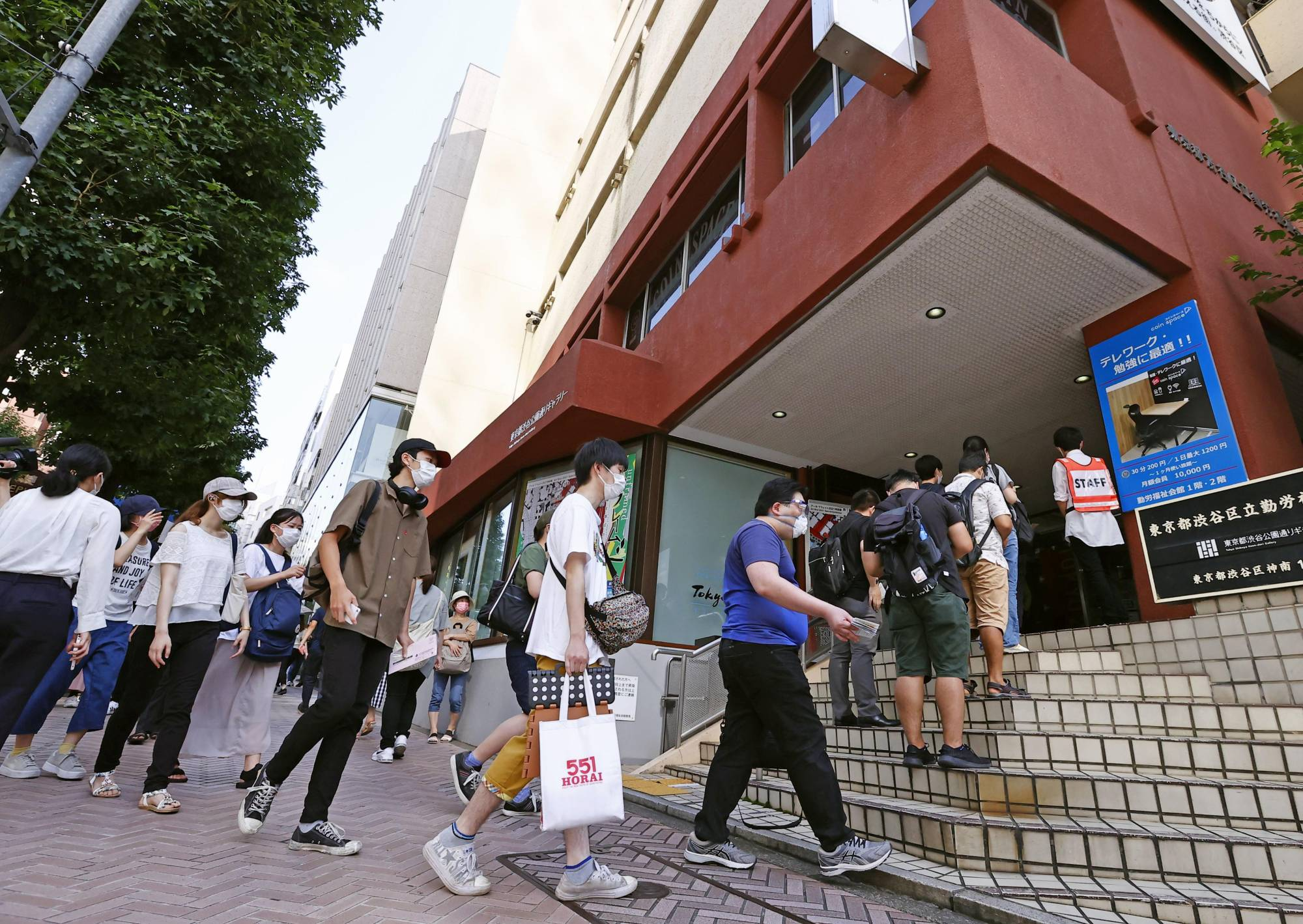 Young people line up at a vaccination center near Tokyo's Shibuya Station on Friday. | KYODO