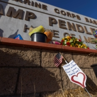 Flowers and other tributes are placed at the main gate to U.S. Marine Base Camp Pendleton in Oceanside, California, on Friday following a deadly suicide bombing at Hamid Karzai International Airport in Kabul a day earlier. | REUTERS