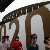 People wearing protective masks walk past the National Stadium, the main venue of the Tokyo 2020 Paralympic Games. | REUTERS