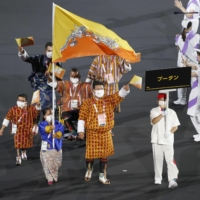 Bhutan's Paralympic delegation marches in the Parade of Nations during the opening ceremony at National Stadium on Tuesday.  | KYODO
