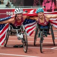 Bronze medalist Tatyana McFadden (left) and gold medalist Susannah Scaroni celebrate after the women's T54 5000 meters on Saturday.  | AFP-JIJI