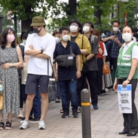 Thousands of young people line up in Shibuya on Saturday to get tickets for about 300 COVID-19 vaccine shots offered for the day. | KYODO