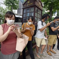 People check the results of a vaccine lottery in Tokyo's Shibuya Ward on Saturday.    KYODO