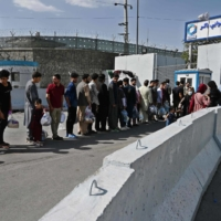 Afghans hoping to leave Afghanistan line up at the main entrance gate of Kabul airport on Saturday.   AFP-JIJI