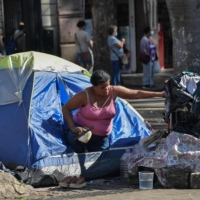 A homeless woman is seen at Se Square in Sao Paulo on Aug. 19.  | AFP-JIJI
