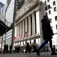 Pedestrians are seen on Wall Street outside the New York Stock Exchange (NYSE) in New York City on March 19.   REUTERS