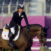 Mitsuhide Miyaji strokes his horse after competing in the equestrian Dressage Individual Test Grade II event at the Tokyo Paralympics on Thursday. | KYODO