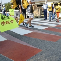 Children Monday walk on a crosswalk that appears to be floating in the air to catch the attention of drivers in front of Chiyokawa Elementary School in Kameoka, Kyoto Prefecture. | KYODO