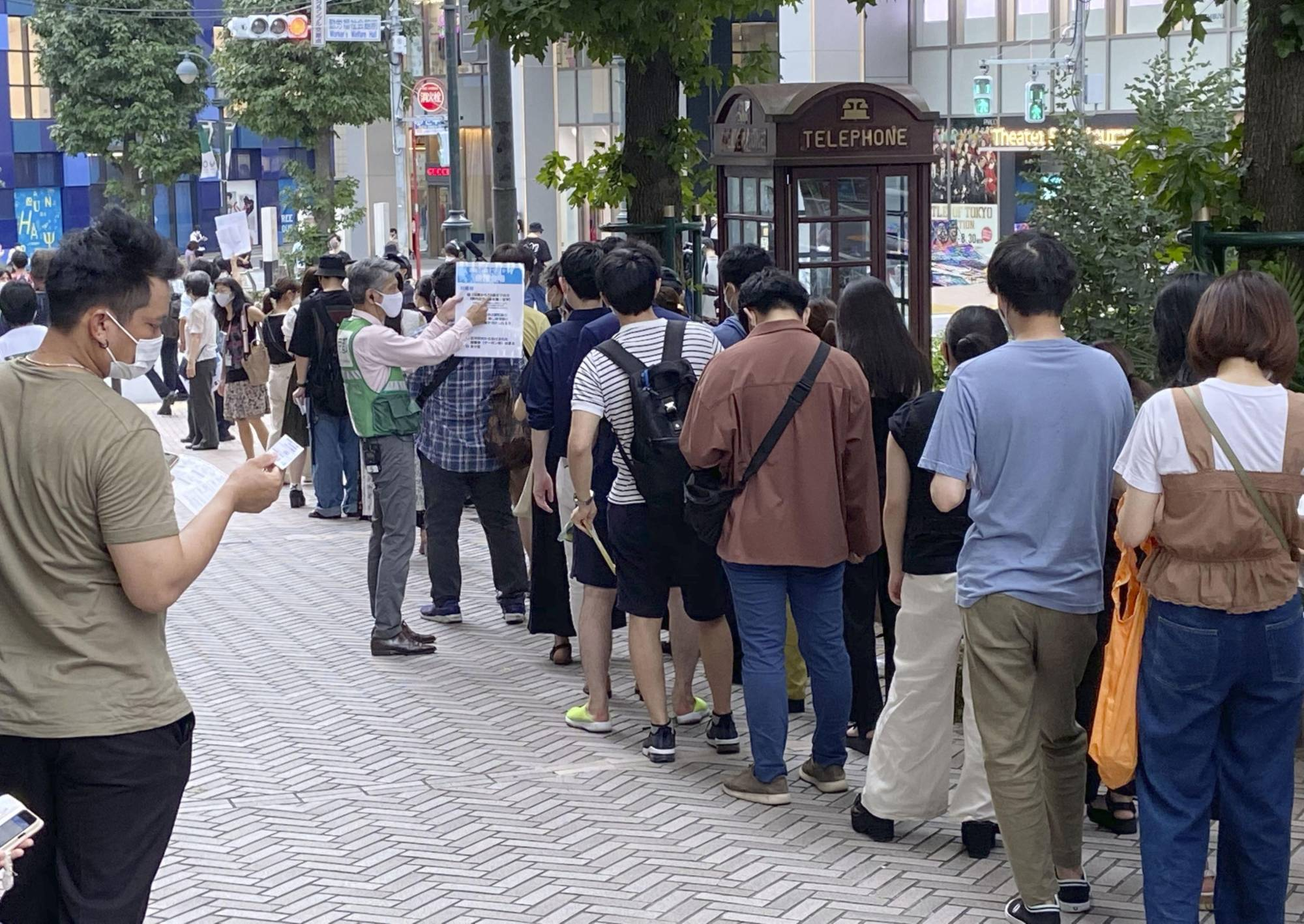People line up in Tokyo's Shibuya Ward on Sunday to obtain a lottery ticket to get vaccinated.   KYODO