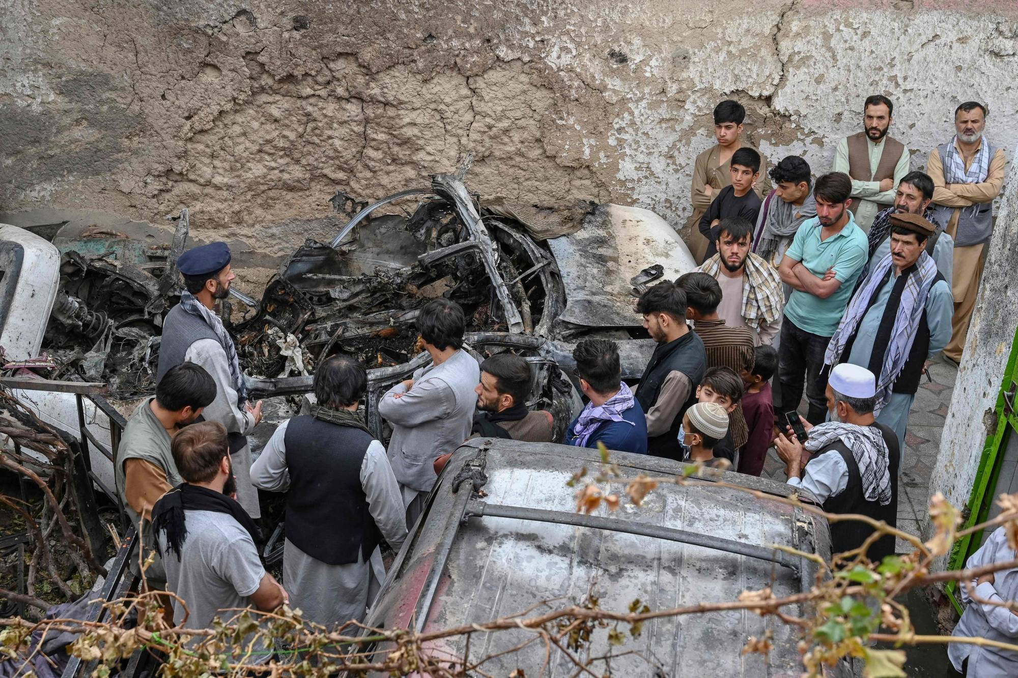 Afghan residents and family members of the victims gather next to a damaged vehicle inside a house in Kabul on Monday, a day after a U.S. drone airstrike.   AFP-JIJI