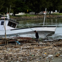 A fishermen checks a boat resting among garbage and plastic waste at a port in Banda Aceh, Indonesia. | AFP-JIJI