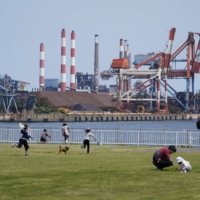 People play at a park as Nippon Steel Corp.'s Kashima plant is in the background in Kamisu, Ibaraki Prefecture, Japan, in April 2020.   BLOOMBERG