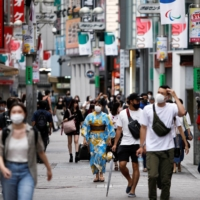 People walk in the Shibuya shopping area during a state of emergency as COVID-19 continues to spread in Tokyo on Sunday. | REUTERS