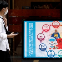 A man looks at infection prevention information displayed in the Shibuya shopping area during a state of emergency as COVID-19 continues to spread in Tokyo on Sunday. | REUTERS