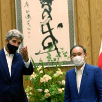 Prime Minister Yoshihide Suga meets with U.S. climate envoy John Kerry in Tokyo on Tuesday. | POOL / VIA AFP-JIJI